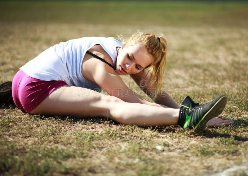 Ung kvinna som gör sträcka övningen, genomkörare på gräs arkivfoto