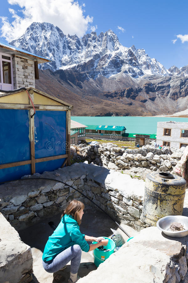 Ung kvinna som gör tvätterit på bergbyn arkivfoton