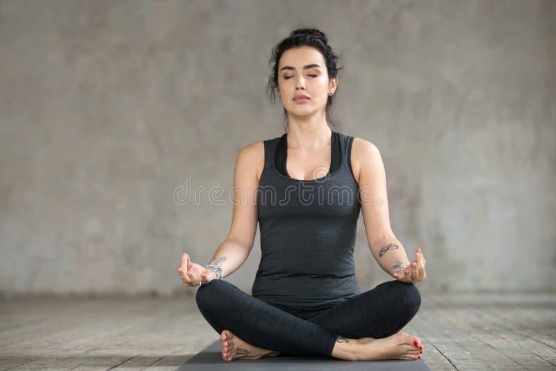 Ung kvinna som gör upp den Sukhasana övningen, slut arkivfoton