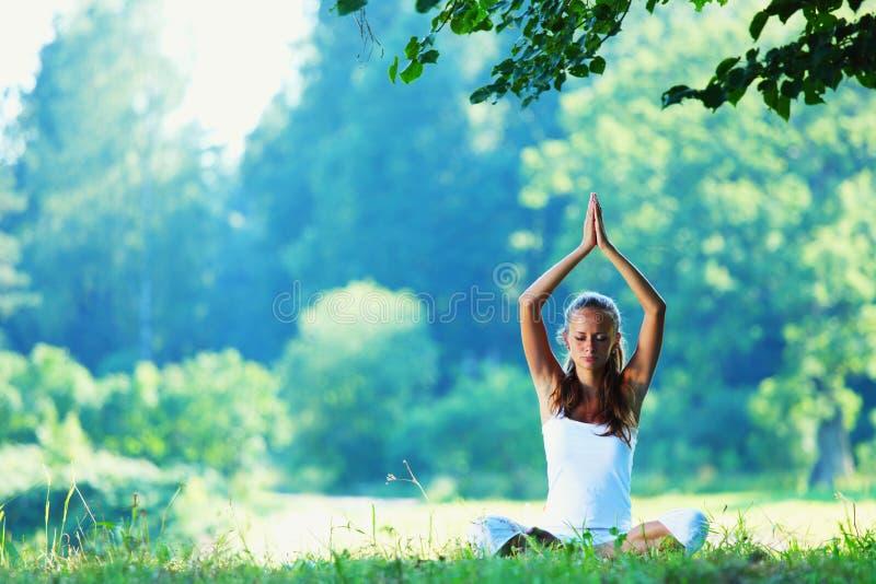 Ung kvinna som gör yogaövning royaltyfri foto