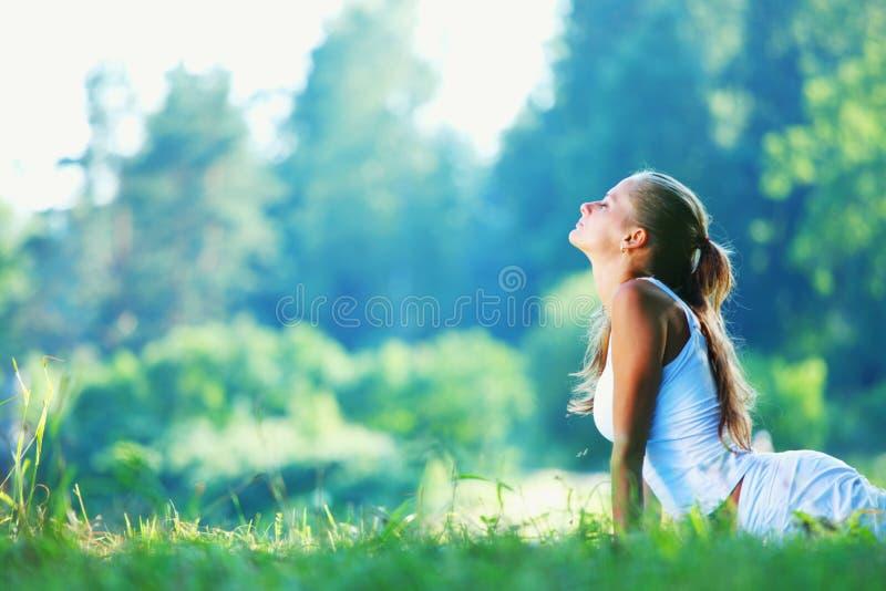 Ung kvinna som gör yogaövning arkivbilder