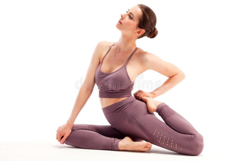 Ung kvinna som gör yogaövning som isoleras på vit bakgrund arkivbild