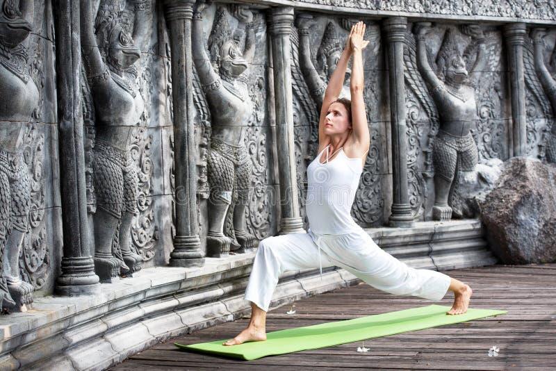 Ung kvinna som gör yoga i övergiven tempel på träplattformen övning arkivfoton
