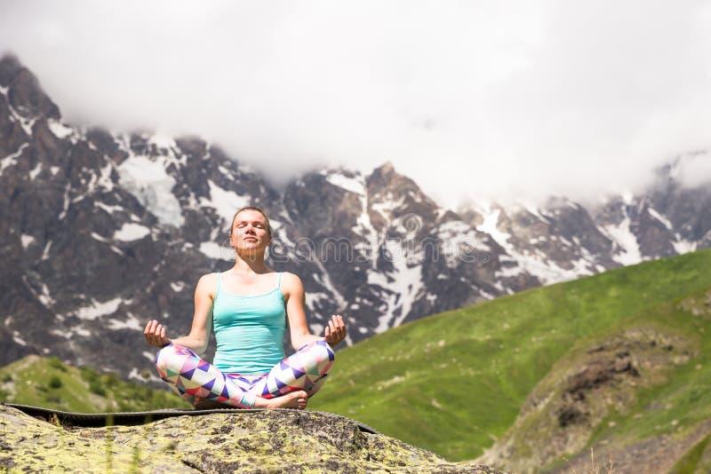 Ung kvinna som gör yoga i härliga berg trevlig sikt royaltyfri foto