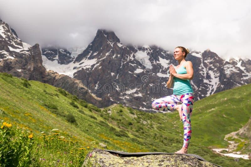 Ung kvinna som gör yoga i härliga berg trevlig sikt royaltyfria bilder