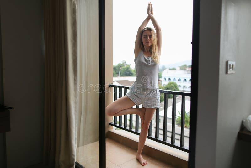 Ung kvinna som gör yoga på balkongen i morgon, bärande sommarpyjamas royaltyfri bild