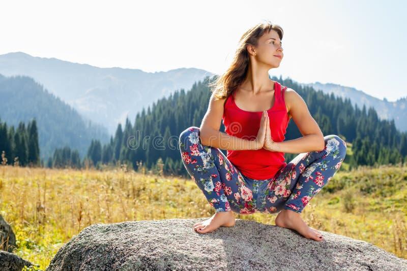 Ung kvinna som gör yoga på en vagga royaltyfria bilder