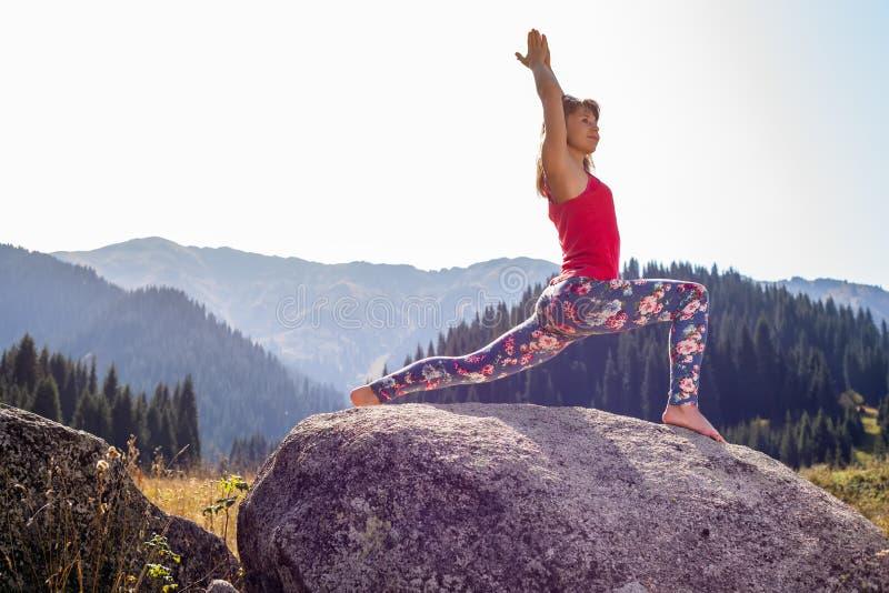Ung kvinna som gör yoga på en vagga arkivfoto
