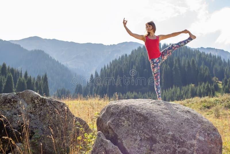 Ung kvinna som gör yoga på en vagga royaltyfri foto
