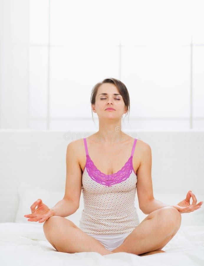Ung kvinna som gör yoga på underlag arkivbild