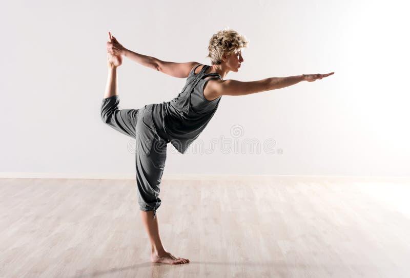 Ung kvinna som gör yoga som balanserar övningar royaltyfri foto