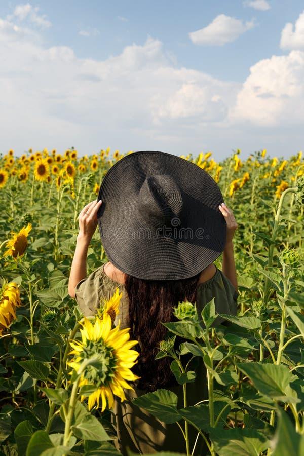 Ung kvinna som g?r i f?ltet med solrosor H?rlig ung flicka som tycker om naturen p? f?ltet av solrosor p? solnedg?ngen arkivfoton