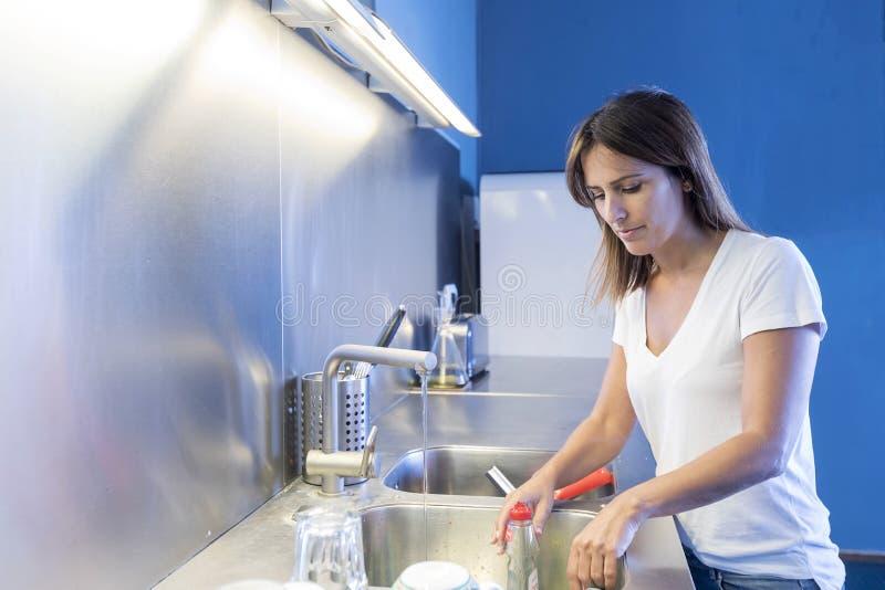 Ung kvinna som g?r ren vasken p? k?ket royaltyfria bilder