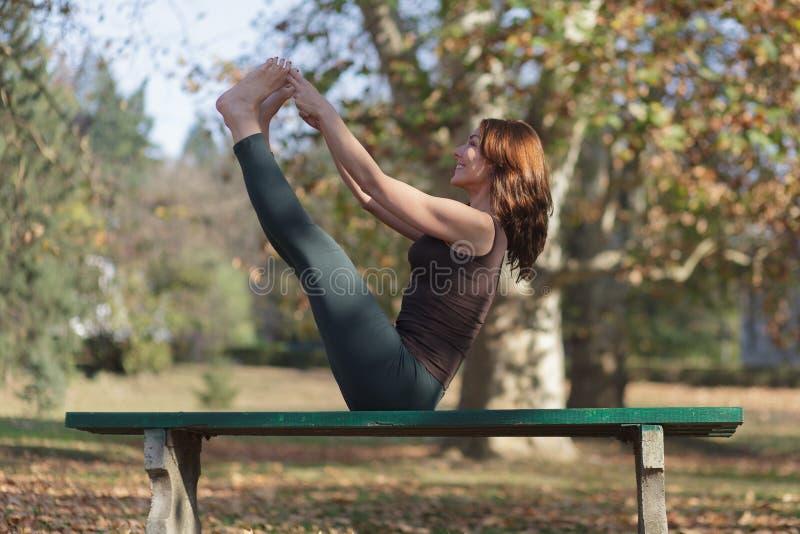 Ung kvinna som g?r yoga i parkera fotografering för bildbyråer