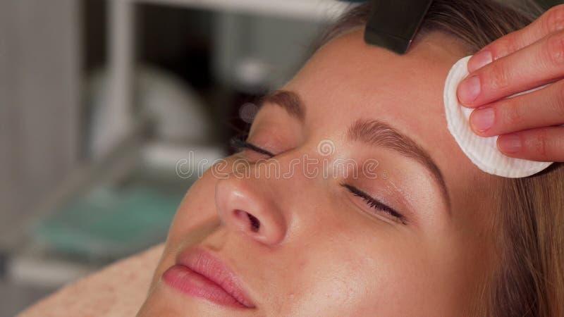Ung kvinna som genomgår ultraljuds- ansikts- behandling på skönhetsalongen fotografering för bildbyråer