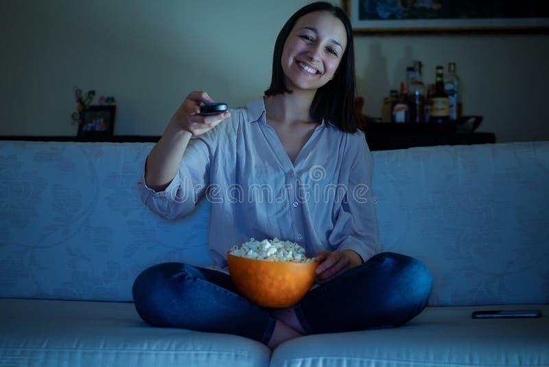 Ung kvinna som håller ögonen på hennes favorit- program på tv royaltyfria foton