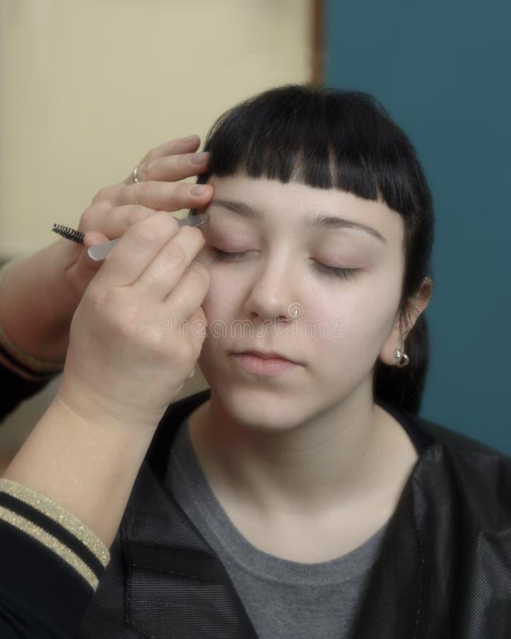 Ung kvinna som har ögonbrynkorrigering fotografering för bildbyråer