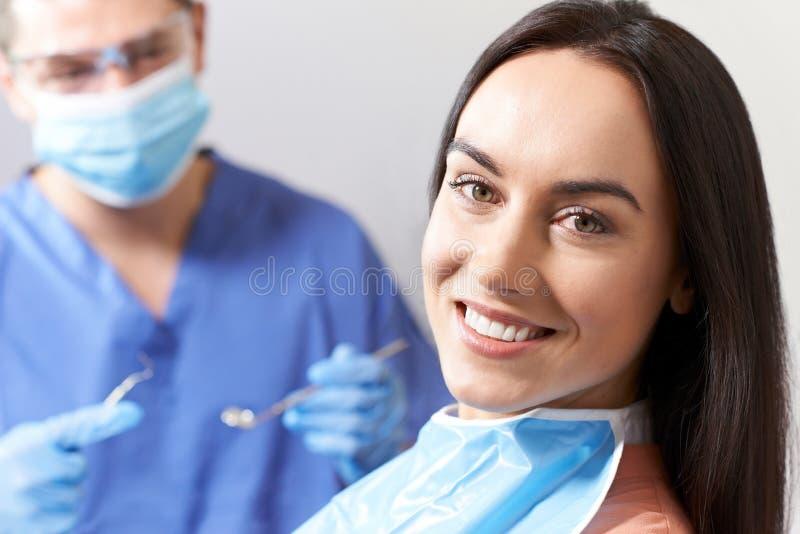 Ung kvinna som har övre och tand- examen för kontroll på tandläkaren arkivbild