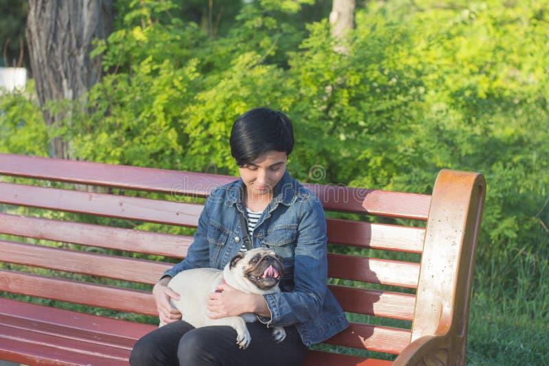 Ung kvinna som har bra tid med mops på det gröna gräset, den nätta flickan med hundlek i parkera under solnedgång eller soluppgån arkivfoton