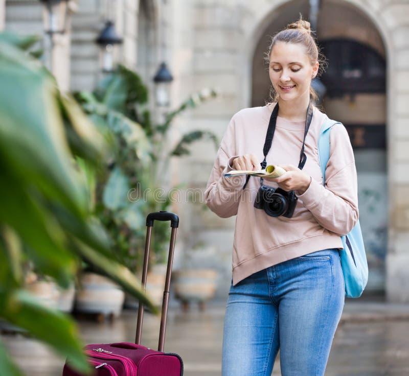 Ung kvinna som har broschyren som söker efter rutten arkivbild