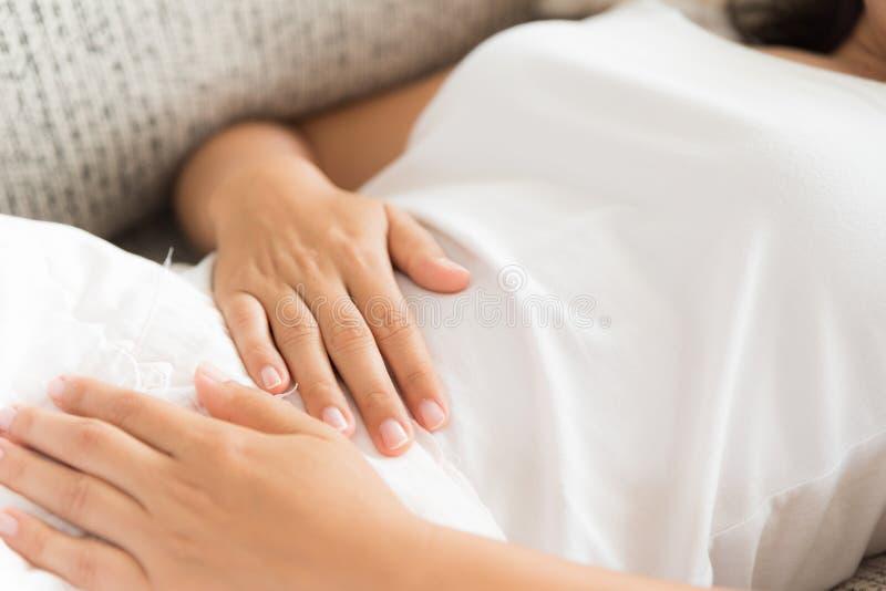 Ung kvinna som har det smärtsamma magknipet som hemma ligger på soffan royaltyfria bilder