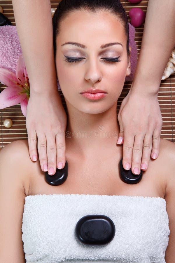 Ung kvinna som har en massage med stenen i en brunnsort royaltyfri bild