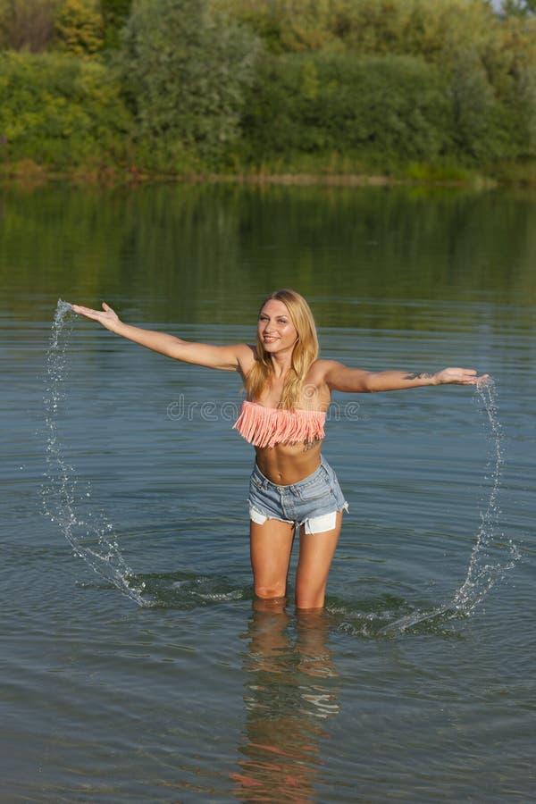 Ung kvinna som har gyckel i vattnet royaltyfri foto
