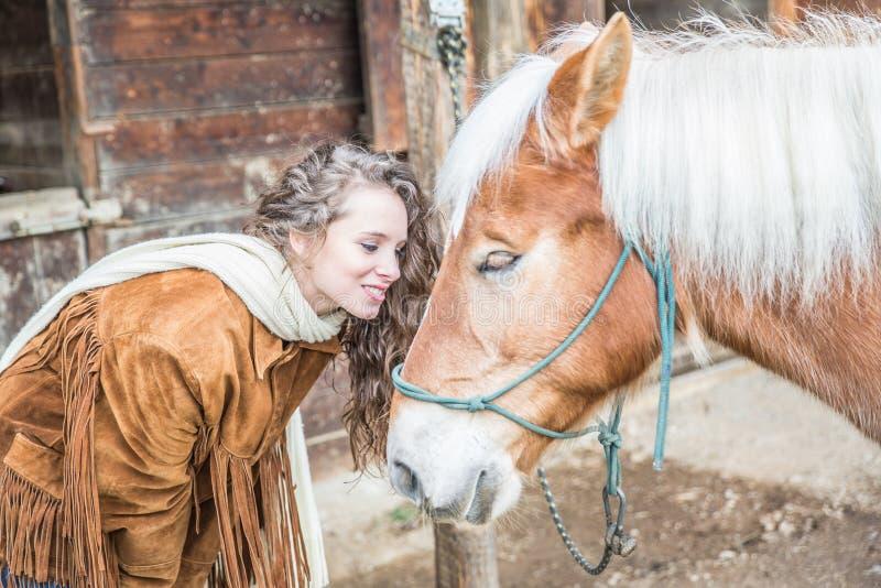 Ung kvinna som har gyckel med hennes häst royaltyfri foto