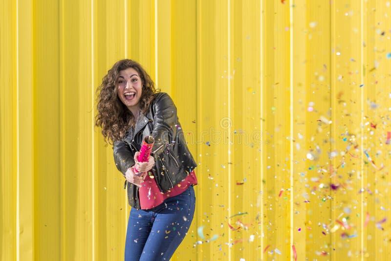 Ung kvinna som har gyckel med konfettier över gul bakgrund arkivbilder