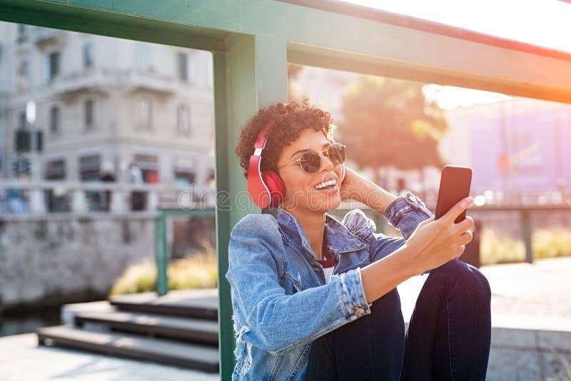 Ung kvinna som har gyckel med musik arkivbild