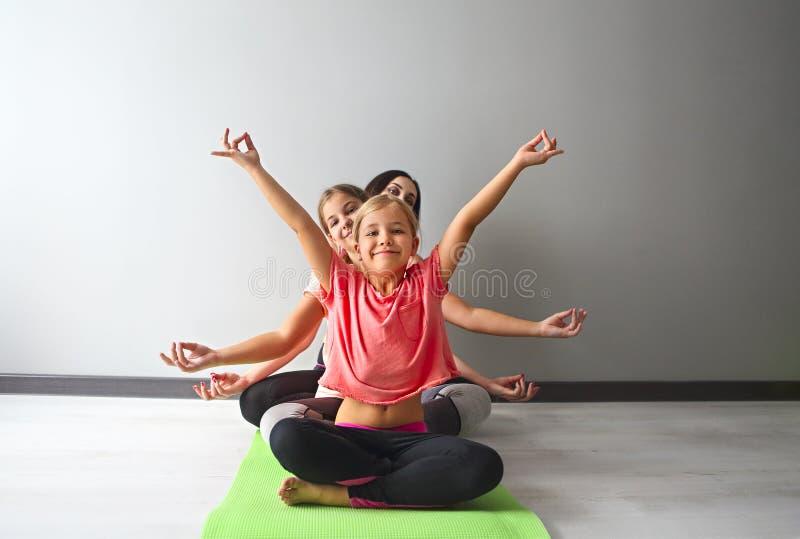 Ung kvinna som har gyckel med ungar som gör yoga royaltyfri fotografi