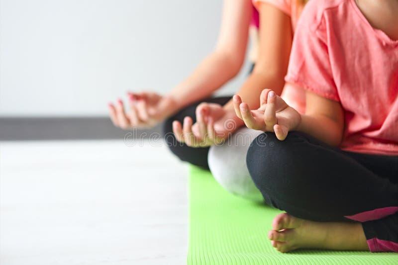 Ung kvinna som har gyckel med ungar som gör yoga Familjsportconcep royaltyfri foto
