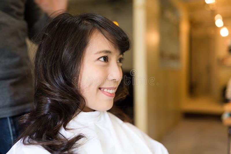 Ung kvinna som har hår att klippas i salong royaltyfria bilder