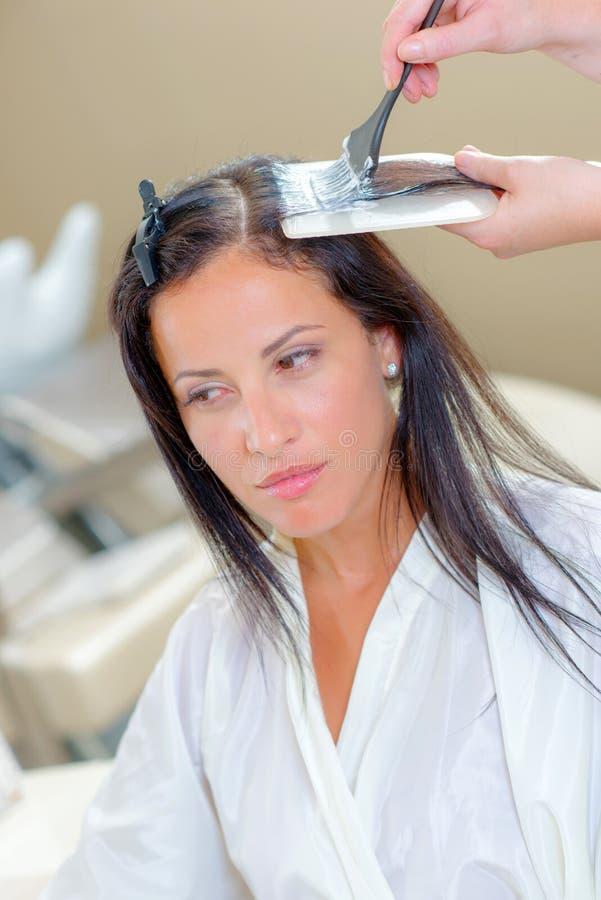 Ung kvinna som har hår att tonas royaltyfri bild