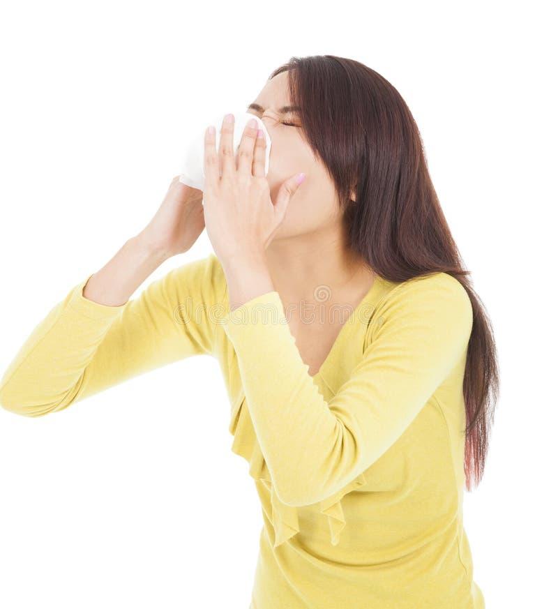 Ung kvinna som har influensa eller allergi och blåser in i silkespapper royaltyfri fotografi