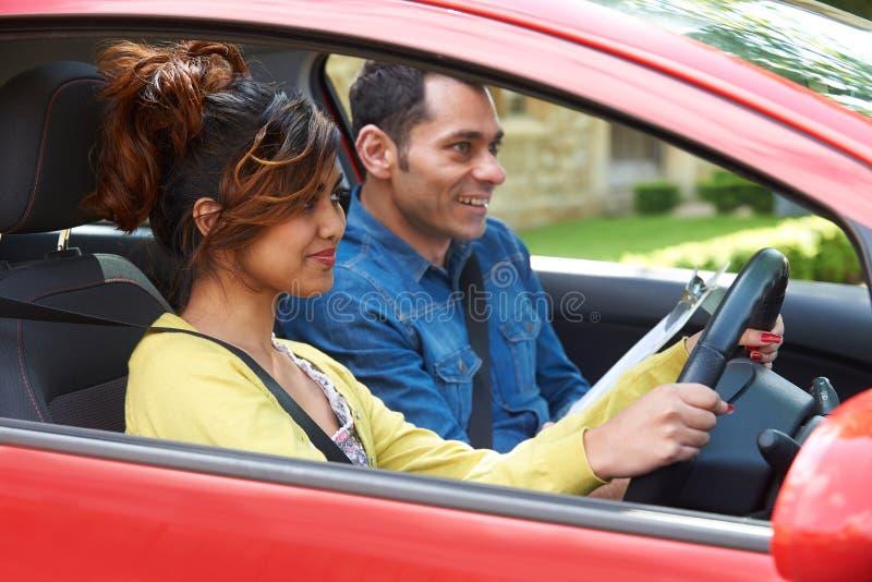 Ung kvinna som har körningskurs med instruktören royaltyfri fotografi
