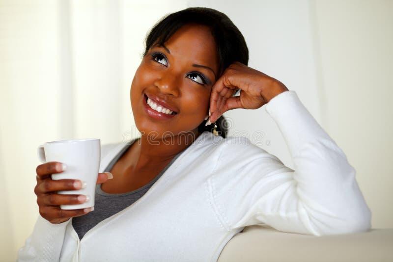 Ung kvinna som har kaffe och att beskåda arkivfoton