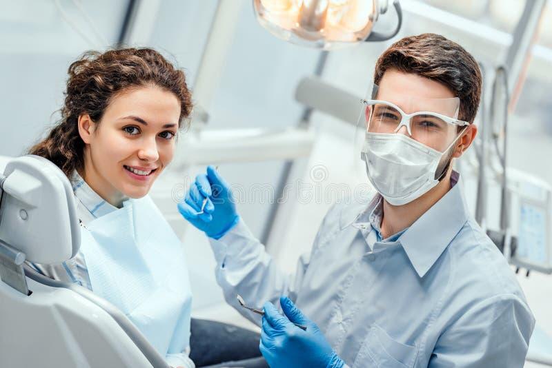 Ung kvinna som har kontrollen upp och tand- examen på den tandläkareSide sikten arkivbild