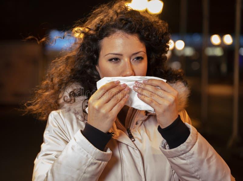 Ung kvinna som har kyla, näsa i rinnande arkivfoto