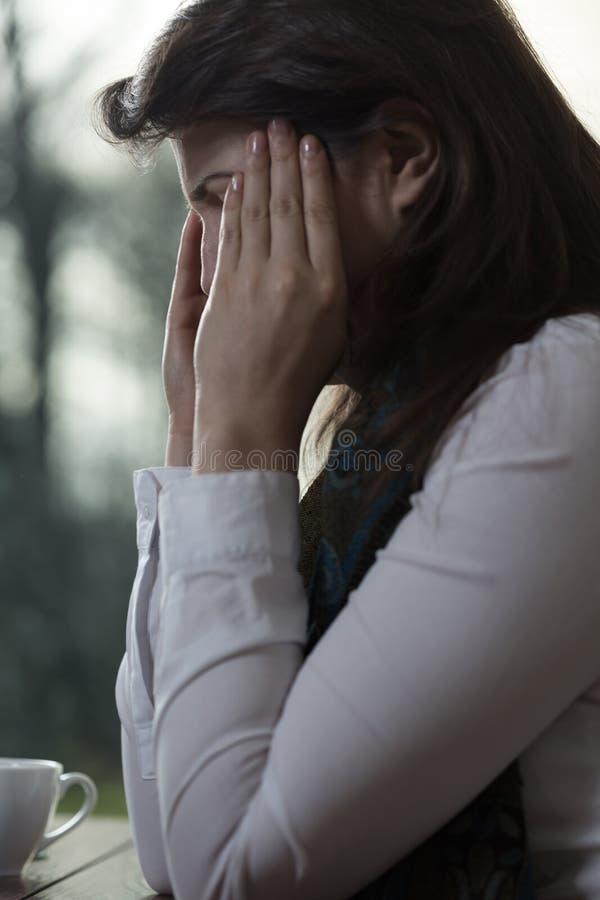 Ung kvinna som har migrän arkivfoto