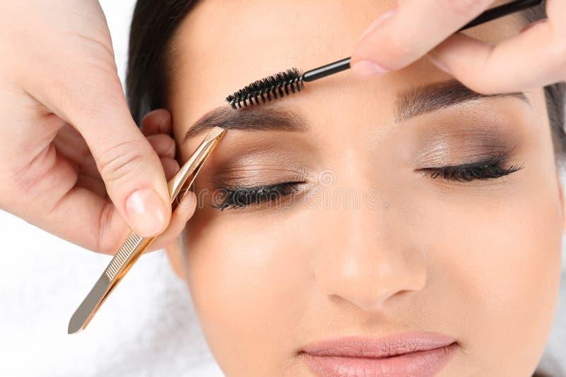 Ung kvinna som har yrkesmässigt ögonbrynkorrigeringstillvägagångssätt i skönhetsalong arkivbild
