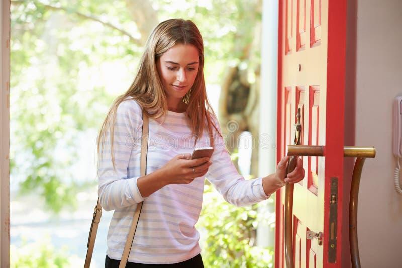 Ung kvinna som hem går tillbaka för arbete som ser mobiltelefonen royaltyfri bild