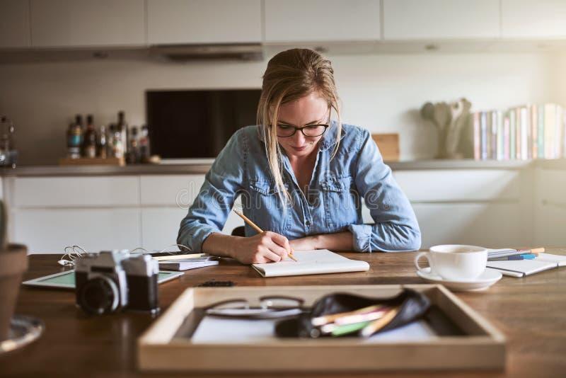 Ung kvinna som hemifrån arbetar och skissar på en notepad arkivbilder