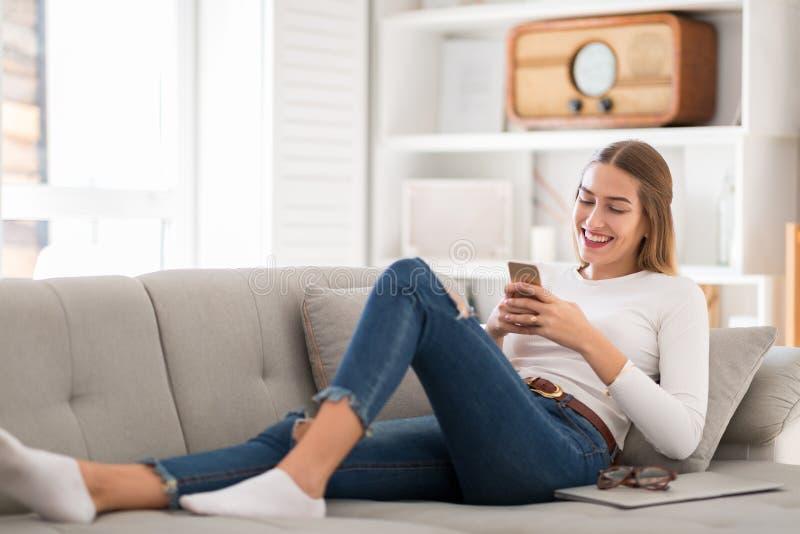 Ung kvinna som hemma använder hennes smartphone royaltyfria foton