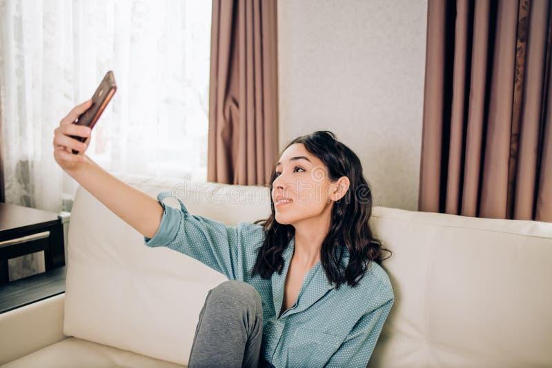 Ung kvinna som hemma använder smartphonen royaltyfri foto