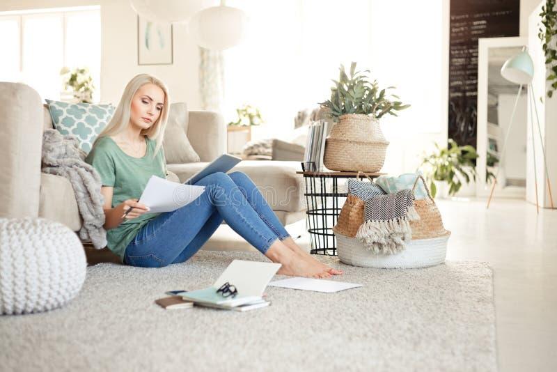 Ung kvinna som hemma arbetar och att sitta på golv i vardagsrum arkivfoto