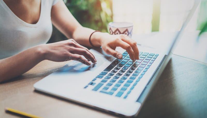 Ung kvinna som hemma arbetar på den moderna datoren, medan sitta på trätabellen Kvinnlign räcker maskinskrivning på bärbar datort royaltyfri foto