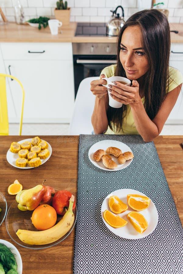 Ung kvinna som hemma dricker kaffe i morgonen royaltyfri foto