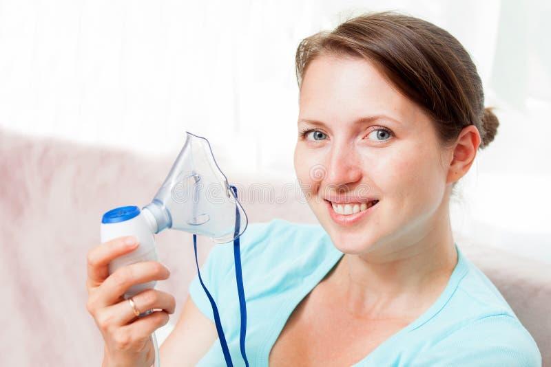 Ung kvinna som hemma g?r inandning med en nebulizer royaltyfria foton