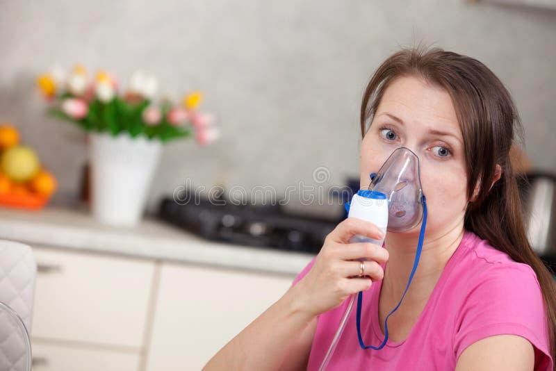 Ung kvinna som hemma g?r inandning med en nebulizer royaltyfri fotografi